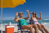 Women relaxing on beach and listening to music